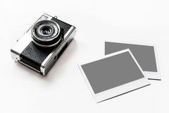 A câmera retro do vintage de Flatlay no fundo branco de madeira com a foto de papel imediata vazia colocou suas imagens Vista sup fotografia de stock royalty free