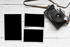 Câmera retro do vintage no fundo de madeira da tabela com fotos vazias Fotografia de Stock Royalty Free