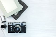 Câmera retro velha e quadros vazios da foto no backgrou de madeira branco Imagens de Stock Royalty Free