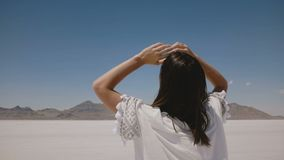 A câmera segue a caminhada feliz bonita da mulher no meio do lago quente ensolarado do deserto de sal de Utá, girando para a câme vídeos de arquivo