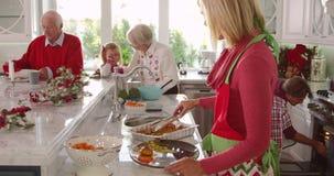 A câmera segue a mãe na cozinha enquanto se junta ao resto da família que prepara o almoço do Natal Preparam vegetais e verificam filme