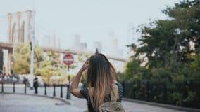 A câmera segue a menina europeia entusiasmado brincalhão do turista com a trouxa nos óculos de sol, aumentando as mãos e 4K feliz filme