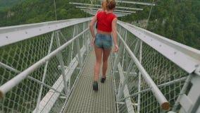 A câmera segue a mulher atlética nova caucasiano que anda na ponte suspendida da treliça alta nas montanhas video estoque