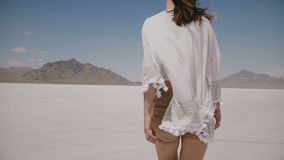 A câmera segue a mulher bonita feliz nova que anda para a frente com o vento que funde na roupa e no cabelo no lago do deserto de video estoque