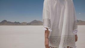 A câmera segue a mulher bonita que anda no meio do lago quente ensolarado do deserto de sal de Bonneville na roupa ocasional leve vídeos de arquivo