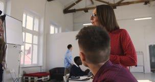 A câmera segue a mulher de negócio envelhecida média do chefe que motiva colegas multi-étnicos no escritório na moda confortável  video estoque