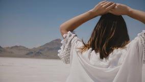 A câmera segue a mulher feliz bonita que aprecia a luz solar no lago quente ensolarado do deserto de sal em Utá, tocando no cabel vídeos de arquivo