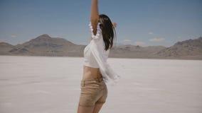 A câmera segue a mulher feliz nova bonita que olha a câmera e que gerencie com os braços abertos no lago do deserto de sal em Utá video estoque