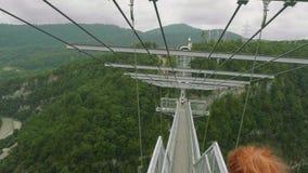 A câmera segue o passeio engraçado da mulher atlética nova caucasiano na ponte suspendida da treliça alta nas montanhas filme