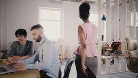 A câmera segue o treinador fêmea afro-americano do negócio entra no escritório, motiva e inspira a equipe multi-étnico 4K dos tra vídeos de arquivo