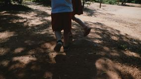A câmera segue os irmãos do rapaz pequeno e da menina que correm no parque unidas que mantém as mãos, jogando e tendo o movimento video estoque