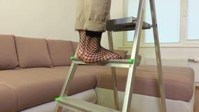 A câmera segue os pés das mulheres que escalam uma escada portátil do metal vídeos de arquivo