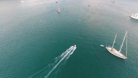 A câmera segue os veleiros infláveis do betweet do barco de motor perto das ilhas pequenas Tiro aéreo do tempo do por do sol de H filme