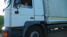 A câmera segue para transportar com o reboque da carga que conduz na estrada e que transporta bens Caminhão que apressa-se atravé filme