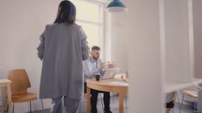 A câmera segue trabalhadores de motivação fêmeas do CEO O chefe da mulher conversa com colegas, dá-lhes sentidos no escritório 4K vídeos de arquivo