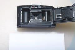 Câmera semiautomática velha Com para trás uma tampa aberta Mentiras em uma superfície branca Perto do papel da foto do caso Vista Foto de Stock