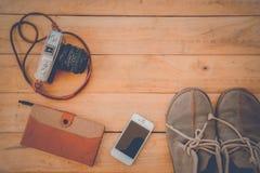 A câmera telefona a sapatas em um vintage de madeira do assoalho Fotos de Stock Royalty Free