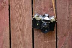 A câmera velha do vintage pesa em uma correia no fundo de uma parede de madeira velha fotos de stock royalty free