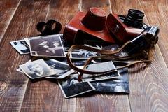 Câmera velha e fotografias velhas no fundo de madeira Foto de Stock Royalty Free