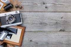 Câmera velha, quadro da foto e filme negativo no fundo de madeira t Fotografia de Stock