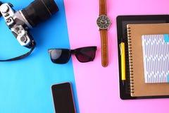 Câmera, vidros, telefone, caderno, diário no fundo do rosa e azul imagens de stock