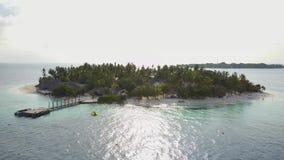 A câmera voa em torno do hotel de resort da ilha tropical redondo pequeno do atol com as palmeiras e turquesa brancas da areia video estoque
