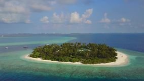 A câmera voa para o hotel de resort da ilha tropical redondo com as palmeiras da areia e Oceano Índico brancos de turquesa sobre video estoque