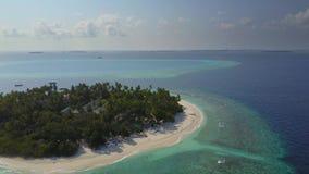 A câmera voa sobre o hotel de resort da ilha tropical com as palmeiras brancas da areia e o Oceano Índico de turquesa em Maldivas vídeos de arquivo