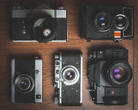Câmeras retros aleatórias na tabela de madeira Imagens de Stock