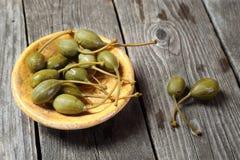 Câpres dans un plat jaune sur une table en bois grise Images stock