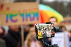 Córrego vivo no telefone esperto, durante a ação do protesto para mostrar a solidariedade com Chechnya's LGBT foto de stock
