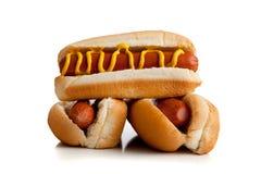 Cães quentes com mostarda em um fundo branco Imagens de Stock Royalty Free