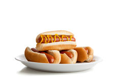 Cães quentes empilhados com mostarda e bolos no branco Imagens de Stock Royalty Free