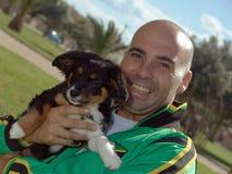 Cão de animal de estimação da terra arrendada do homem Imagens de Stock