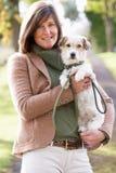 Cão de passeio da mulher ao ar livre no parque do outono Fotografia de Stock Royalty Free
