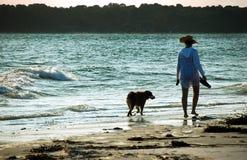 Cão de passeio da mulher na praia no por do sol Imagens de Stock Royalty Free