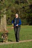 Cão de passeio da mulher sênior fotografia de stock