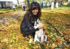 Cão de puxar trenós siberian da jovem mulher e do cão pequeno Foto de Stock Royalty Free