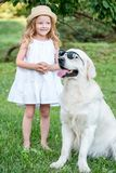 Cão grande engraçado nos óculos de sol e na menina loura bonito no vestido branco fora no parque Imagens de Stock Royalty Free