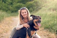 Cão preto de sorriso feliz que veste um chicote de fios de passeio que senta-se enfrentando seu proprietário bonito da jovem mulh imagens de stock royalty free