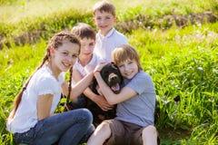 Cão que sorri com três crianças Fotos de Stock
