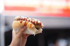 Cão quente Uma mão que guarda o meio cachorro quente da mordida Imagens de Stock