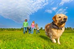 Cão running na frente da família feliz Imagem de Stock Royalty Free