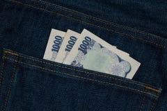 Cédula da moeda do iene japonês em um bolso traseiro de um jea da sarja de Nimes Imagem de Stock