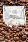 Cédula de 100 dólares americanos, entre grões do café Conceito do negócio para a compra, a venda, a entrega e a distribuição de fotografia de stock