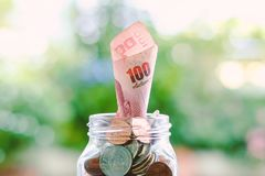 Cédula, dinheiro tailandês de uma moeda de 100 bahts que cresce do ja de vidro Imagens de Stock