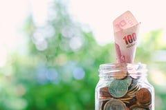 Cédula, dinheiro tailandês de uma moeda de 100 bahts que cresce do ja de vidro Fotos de Stock Royalty Free