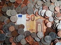 cédula do euro 50 cercada por moedas das moedas de um centavo do dólar Imagem de Stock