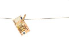 Cédula do Euro 50 que pendura na corda no fundo branco Imagens de Stock
