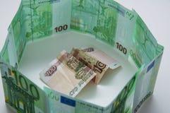 Cédula em cem rublos nas moedas de papel dos arredores em cem euro Imagens de Stock